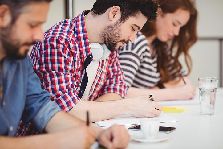 Creative businessman with coworkers writing on documents in meeting room at office