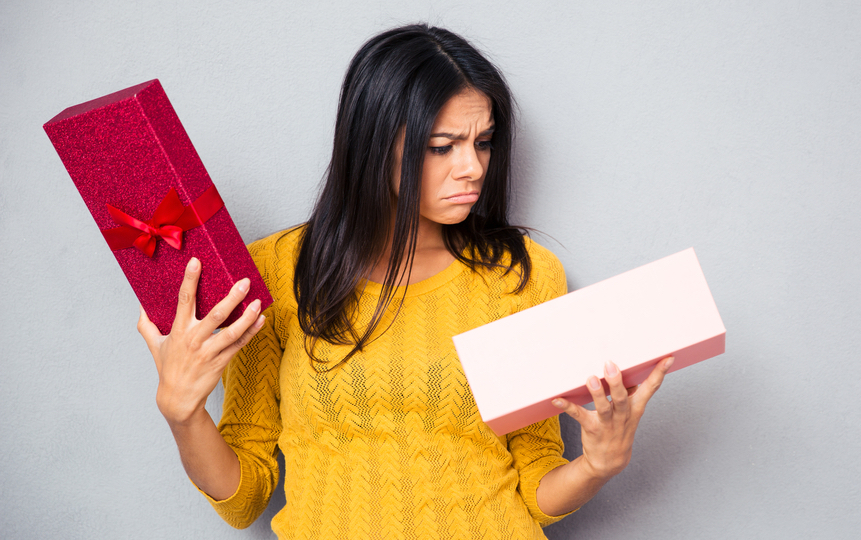 Unhappy young woman holding gift box over gray background-1